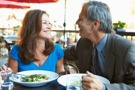 Mature Couple Enjoying Meal At Outdoor Restaurant
